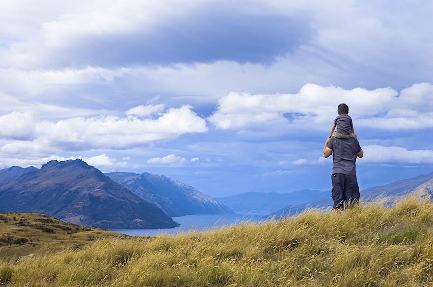 A young kid sits on the shoulders of a man as they overlook the Queenstown scenery