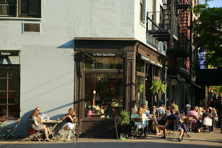 People sit at small tables outside of a cafe on a street in New York City.