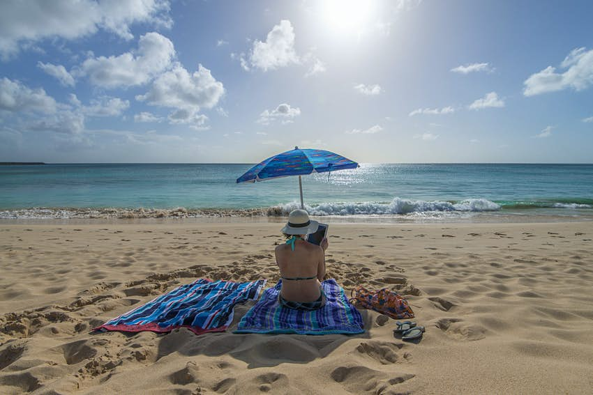 Woman uses digital tablet on uncrowded beach