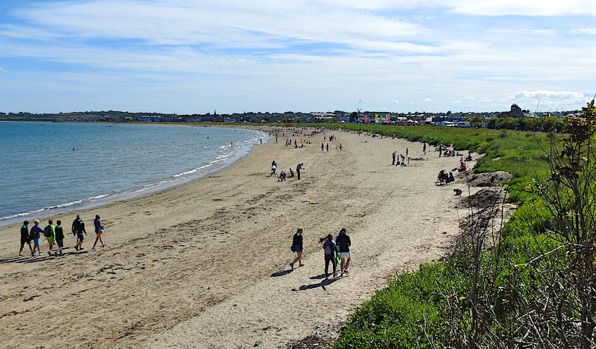 People walk along Skerries Beach on a summer day