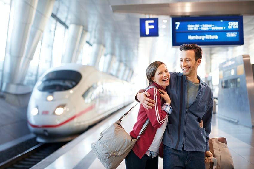 A couple hugging at a German train station with a train in the background