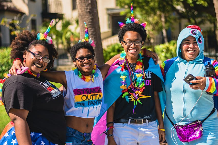 Four people with rainbow colored accessories smile at the camera