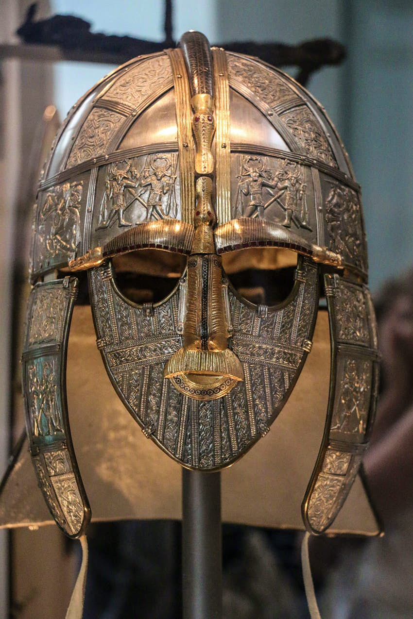 A large metal helmet and face-covering, with engravings of warriors