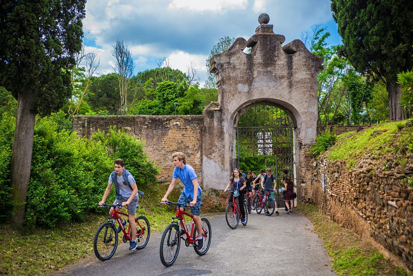 A group of kids bike through the entrance to the catacombs in Rome
