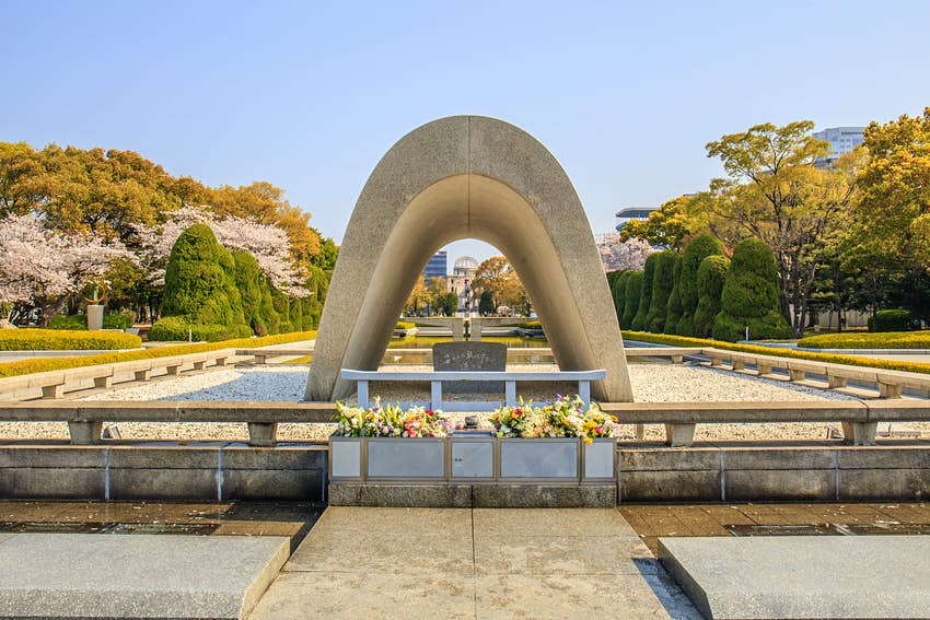 The Memorial Cenotaph at Hiroshima Peace Memorial Park. The cenotaph is a white, smooth monument in a half oval shape.
