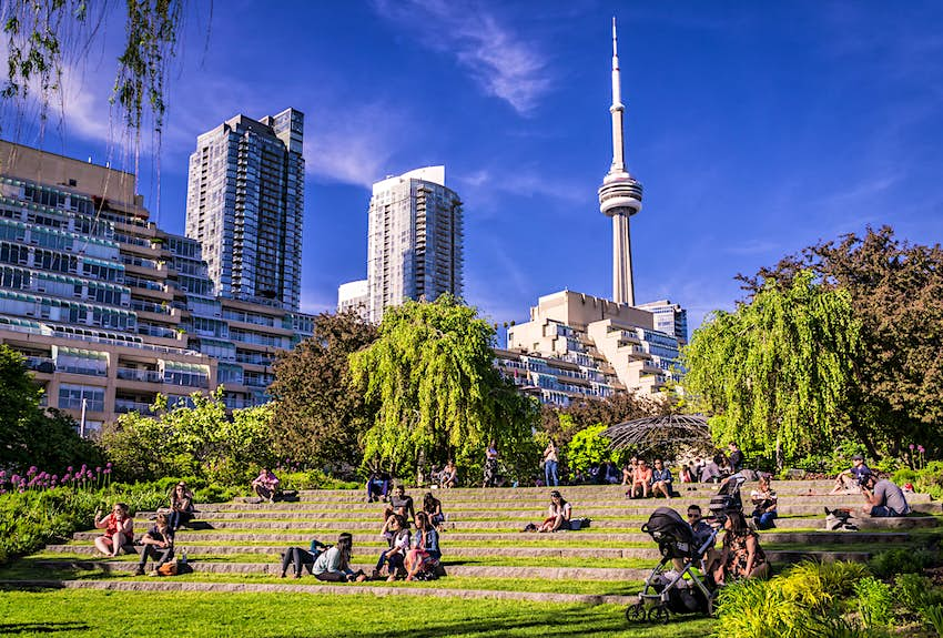 Visitors seated in the Toronto Music Garden on a sunny day