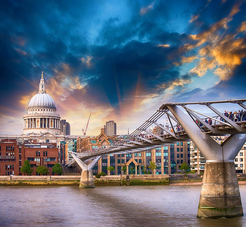 A metal footbridge spans a wide river, leading to a domed church building. There's an atmospheric sky of dark clouds and sunlight.