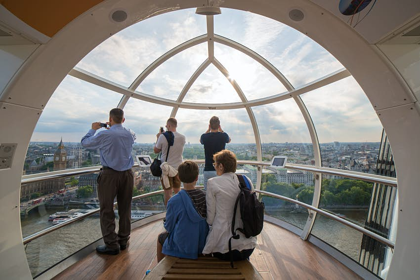 The interior of a glass pod of the London Eye high above London. An older woman and a young boy sit on the bench in the center looking out at the view
