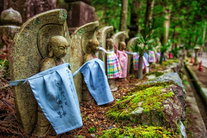 Okunoin Cemetery in Koyasan, Japan. A number of small stone statues are wrapped in fabric, amidst a forest setting.