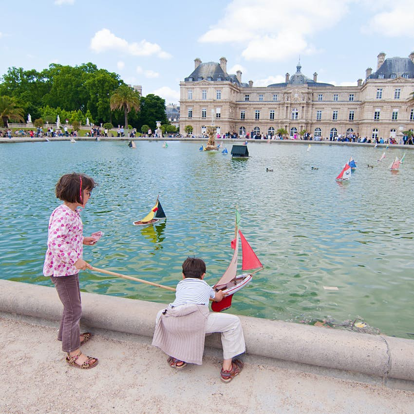 Two children push small sail boats out onto a pond in front of a grand palace building