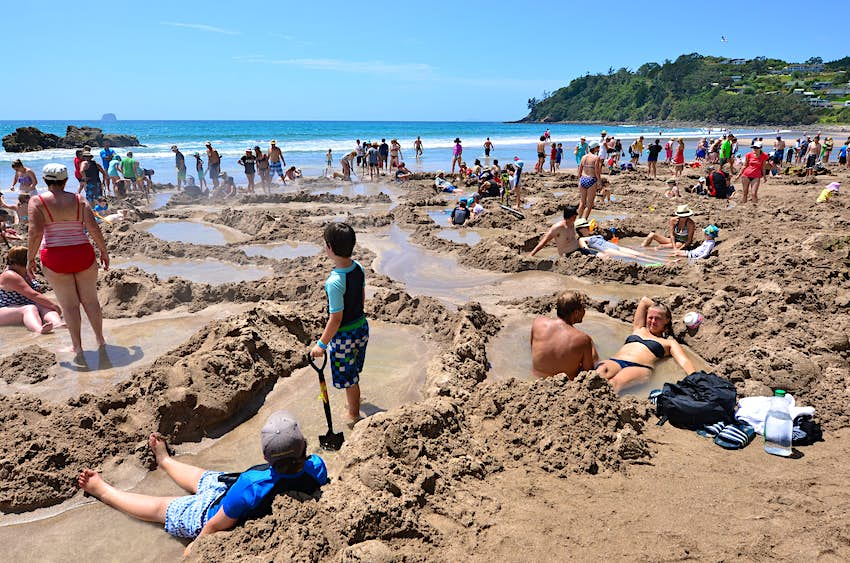 Visitors making small hot water pools in Hot Water beach.it one of the most popular geothermal attractions in New Zealand, about 700,000 people visit the beach annually.