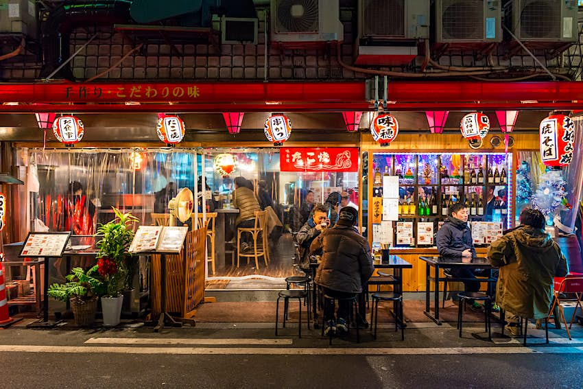 Locals eat at tables set up on the road outside a late night restaurant in Osaka, Japan. The restaurant is lit up in lights and appears bright against the dark night sky.