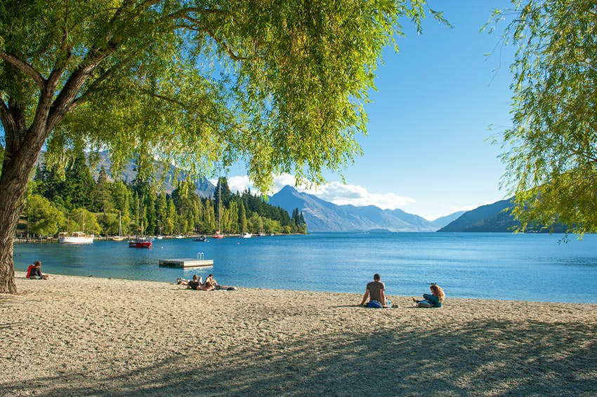 February 15, 2012: Visitors relax on the shore of Lake Wakatipu in Queenstown.