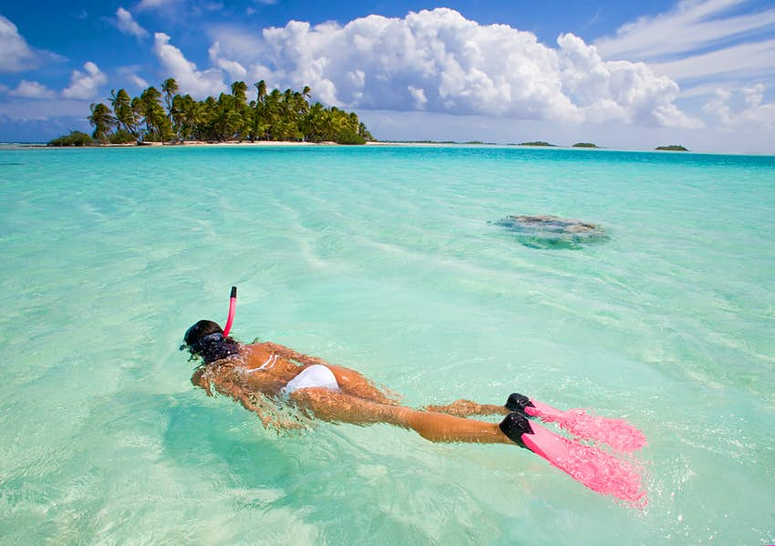 active woman free diving snorkeling in beautiful blue ocean on summer vacation.
