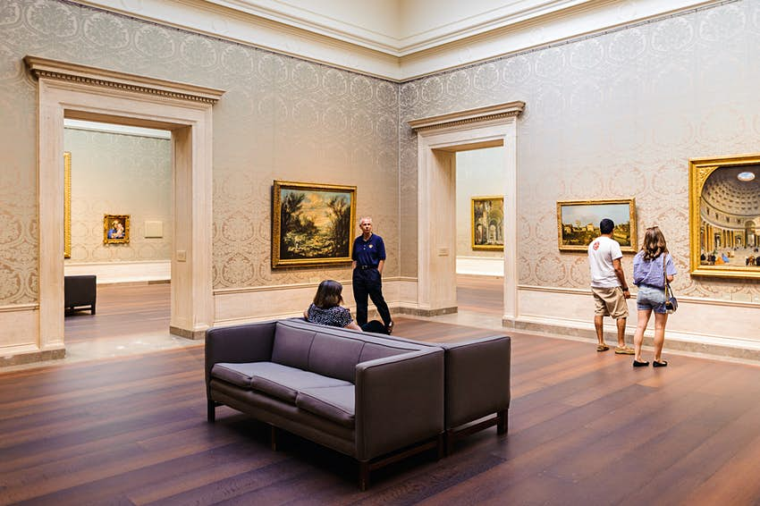 The interior of an art gallery. There is couch in the middle of the room and a few people viewing paintings on the wall.