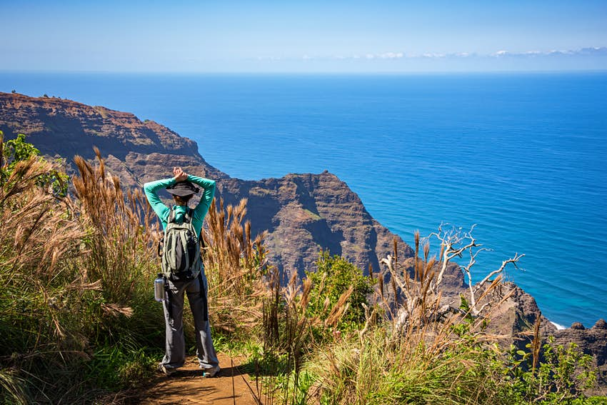 A woman stands at the end of the Awa'awapuhi Trail on Kauai, Hawaii