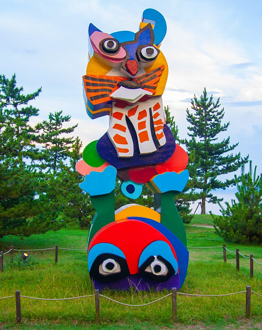 An artistic sculpture resembling a large, colourful cat stands in a field on the island of Naoshima, Japan.