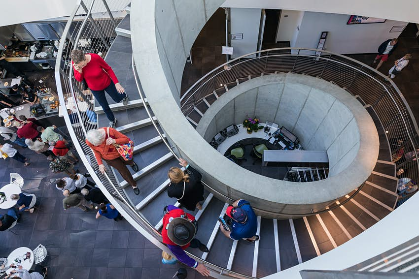 Museum attendees descend a spiral staircase