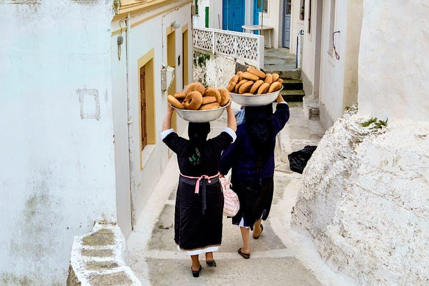 Οι γυναίκες μεταφέρουν μπολ με ψωμί για τον εορτασμό του Πάσχα σε ένα στενό μονοπάτι στον Όλυμπο στο νησί της Καρπάθου