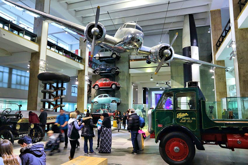 A small plane is suspended from the ceiling of a vast museum room packed with different forms of transport