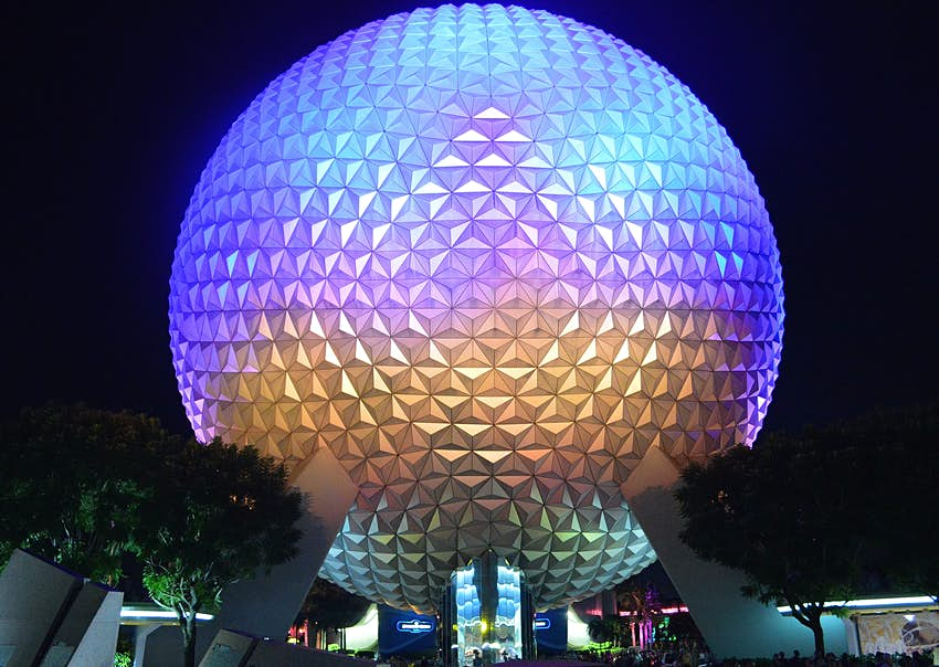 A large silver-gray sphere is illuminated with purple and gold lights against the night sky