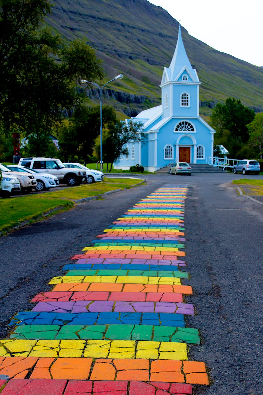 A rainbow brick path leading to a small blue church