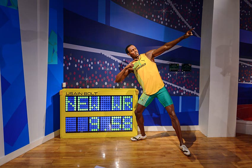 Jamaican athlete Usain Bolt stands in his trademark pose with arms pointing at an angle upwards as he leans, standing next to his world record 100m time of 9.58 seconds