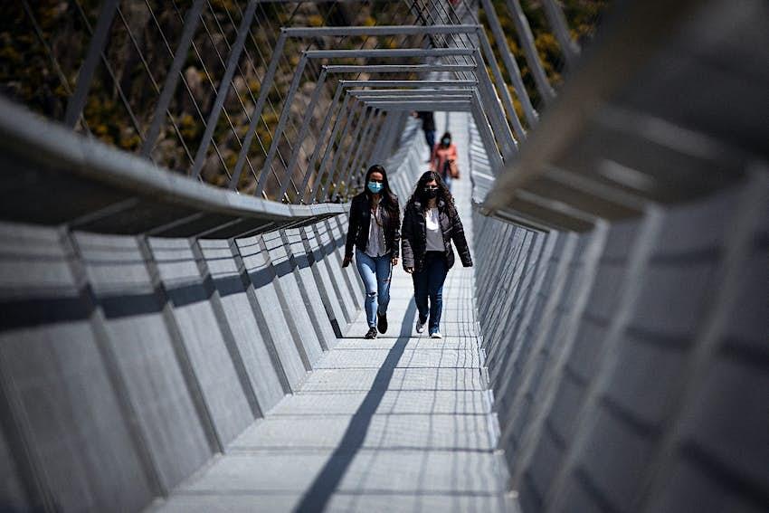 People wearing masks crossing the 516 Arouca Bridge in Portugal, the world's longest pedestrian suspension bridge