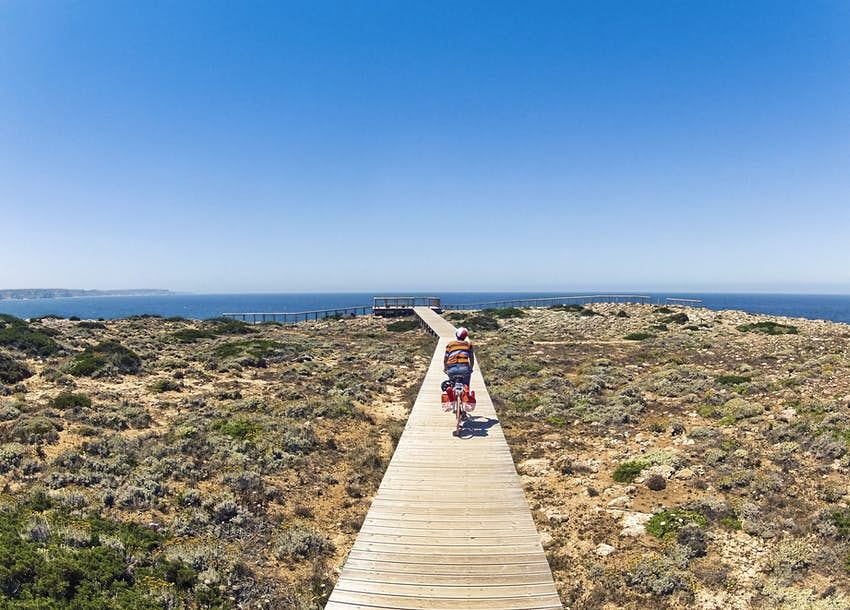 A young woman cycling on a narrow wooden promenade in Carrapateira, Portugal.  In the distance, the blue sea is visible.