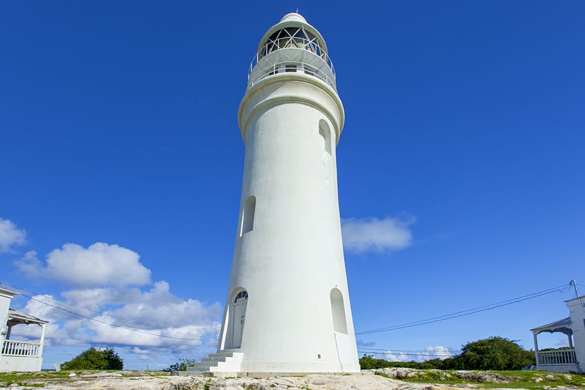 Exterior shot of the white, stone Dixon Hill Lighthouse in San Salvador, Bahamas