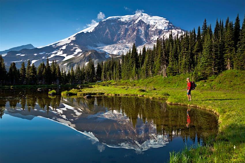 WASHINGTON - Hiker  reflecting in a small tarn below Curtis Ridge next to the Wonderland Trail in Mount Rainier National Park.