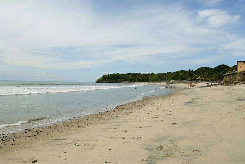 A wide angled view of El Palmar Beach in Panama. The beach is sandy and gently slopes down into a gentle sea. A few families stand around on the sand in the distance.