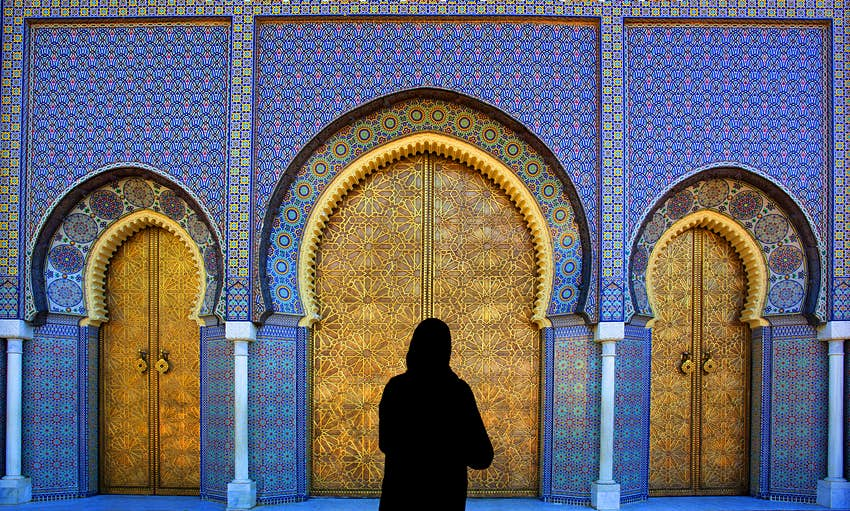 Woman standing at brass doors in Fez, Morocco