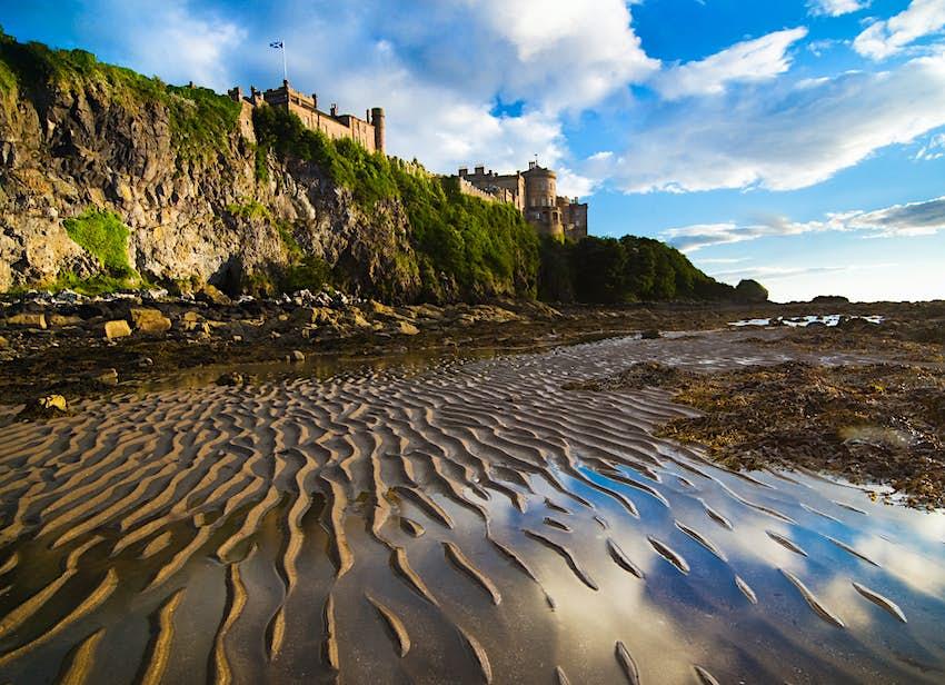A clifftop castle with a sandy beach below it