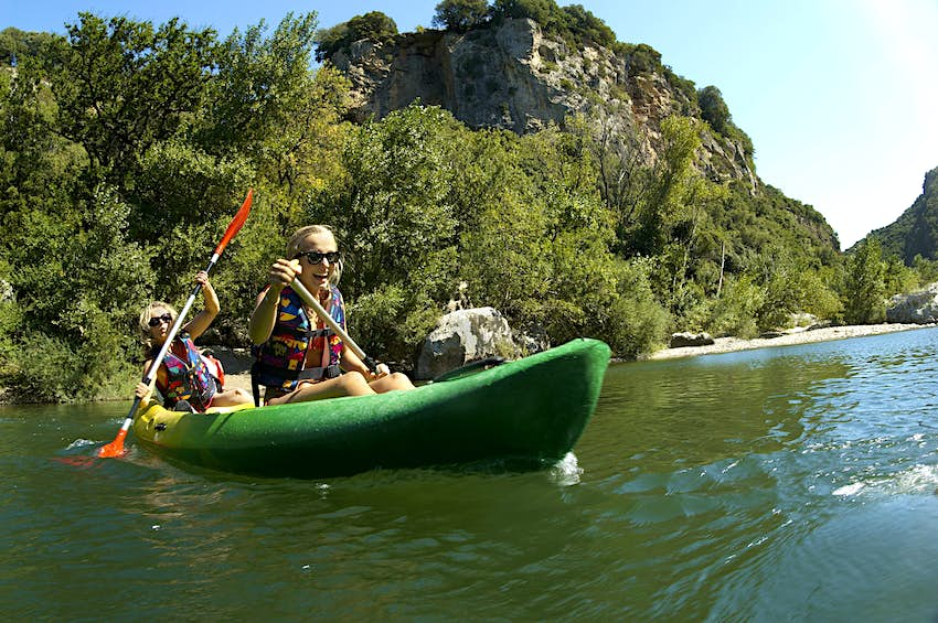Young girl and mother laughing as they steer a kayak through a gorge