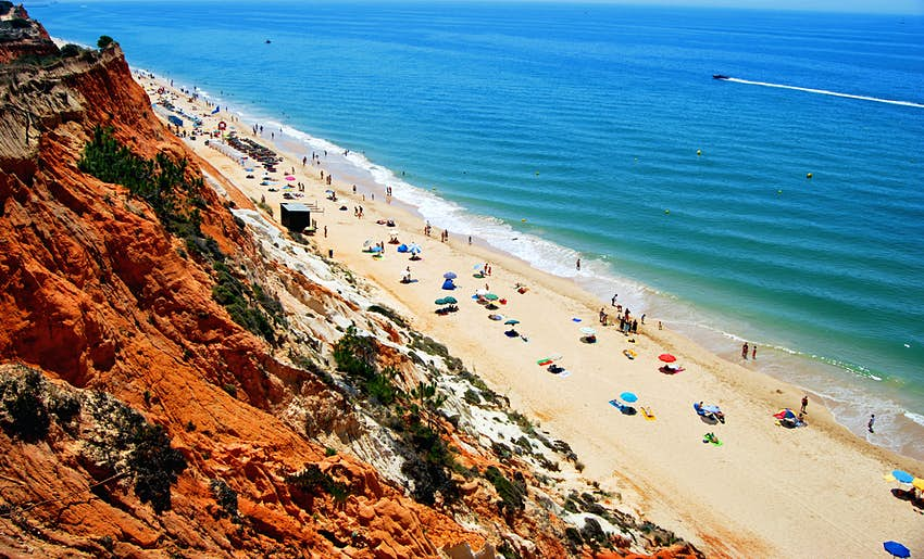 An overhead view of Praia da Falesia in Portugal. The thin strip of golden sand is full of people sunbathing. Behind the sand is bright brown cliffs and in front is a turquoise sea.