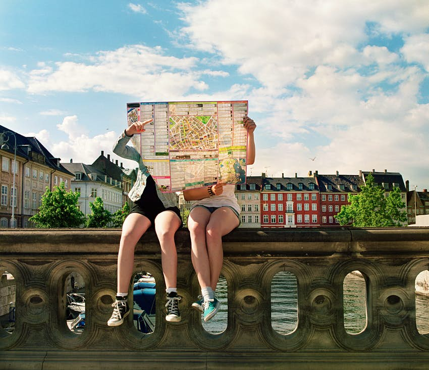Teenagers sitting on a city wall hidden by city map