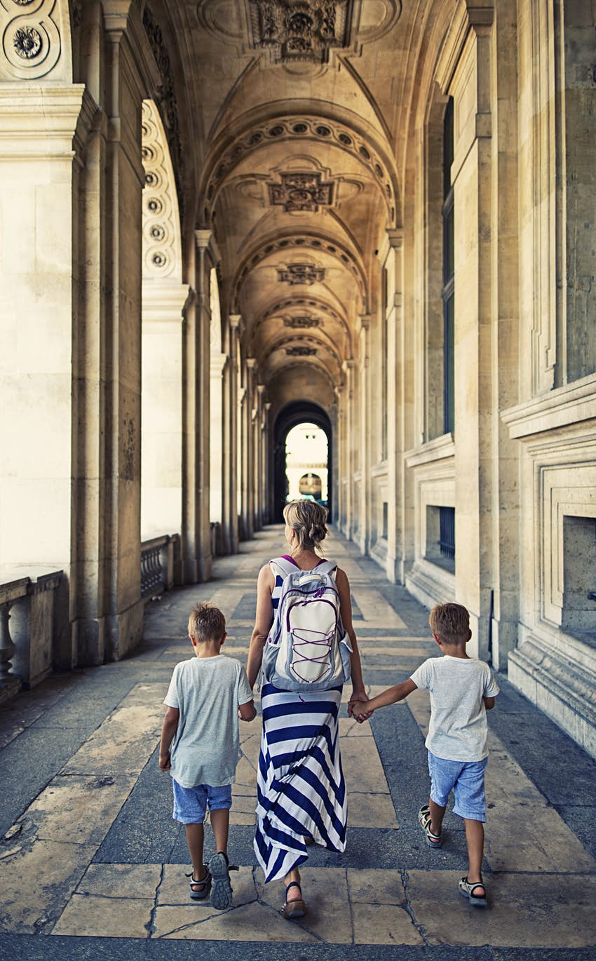 Rear shot of a woman walking along an arched arcade while holding hands with two small children