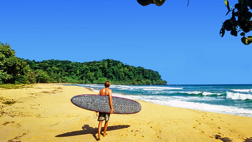 A surfer with a board under his arm walks down the beach towards the blue ocean that is full of breaking waves.