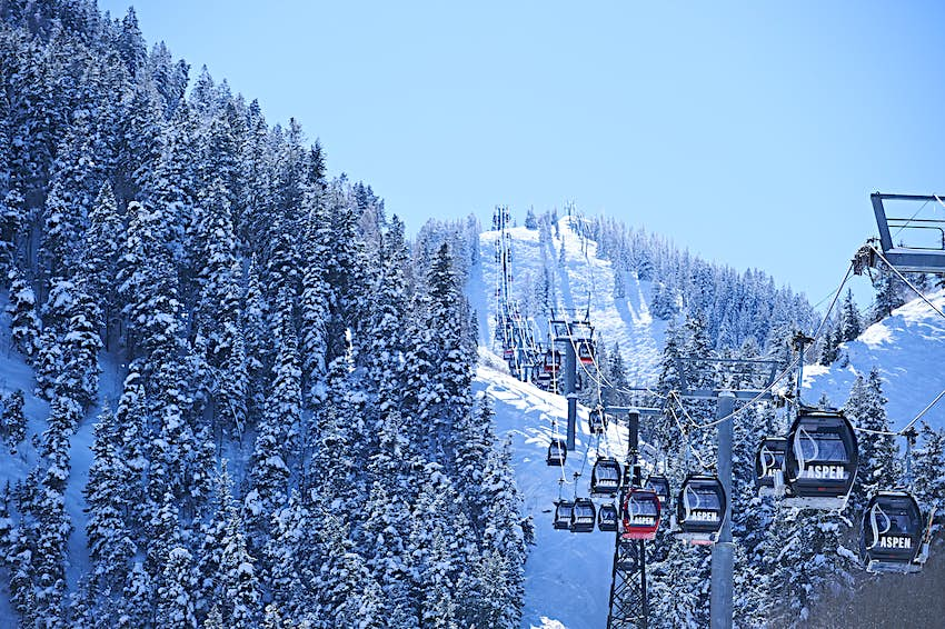 Cable car moving up over forested snow covered mountains in Aspen, Colorado