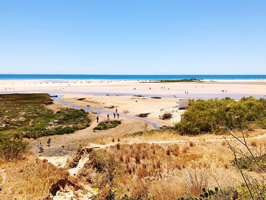 A sweeping view of the beaches of the island of Tavira, a narrow sandy strip of land off the south coast of Portugal. The island is ringed by beautiful sandy beaches.