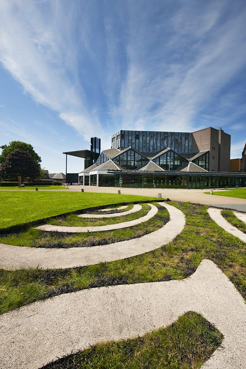 A glass-and-concrete building set in pristine landscaped gardens