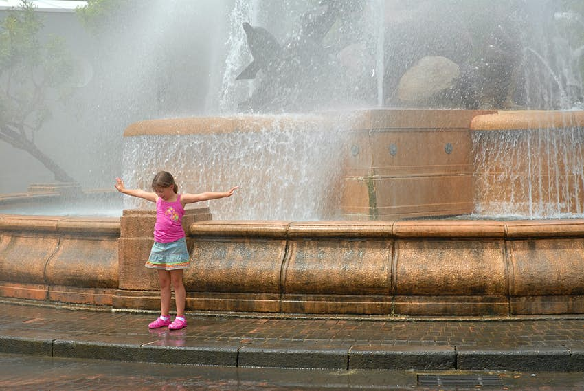 A young girl cooling off in the fountain mist in Old San Juan Puerto Rico