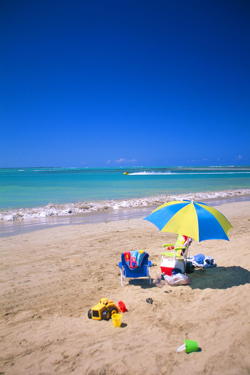 A beach chair and blue and yellow umbrella rest on the sand next to an ice cooler. There is a toy truck and small pails next to it.