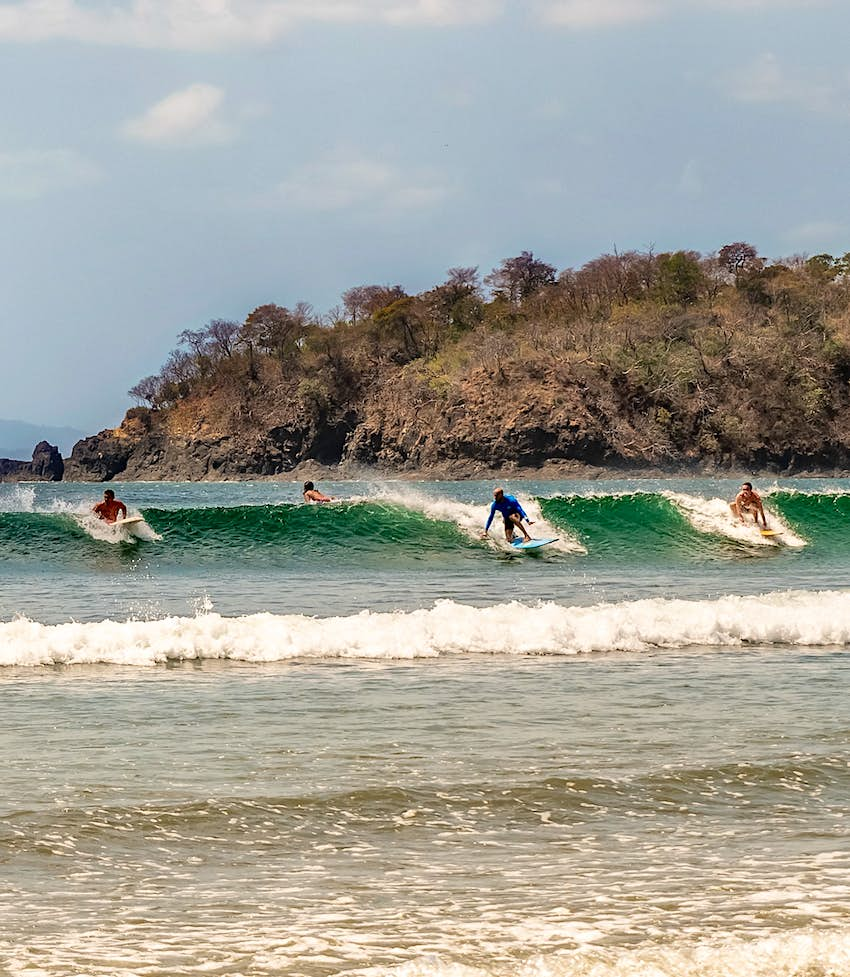 Four people ride a wave at Venao Beach, a popular surf spot in Panama.