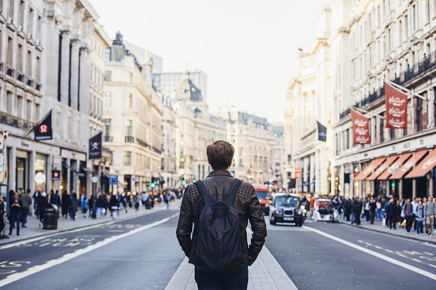 Tourist with backpack walking on Regent Street in London