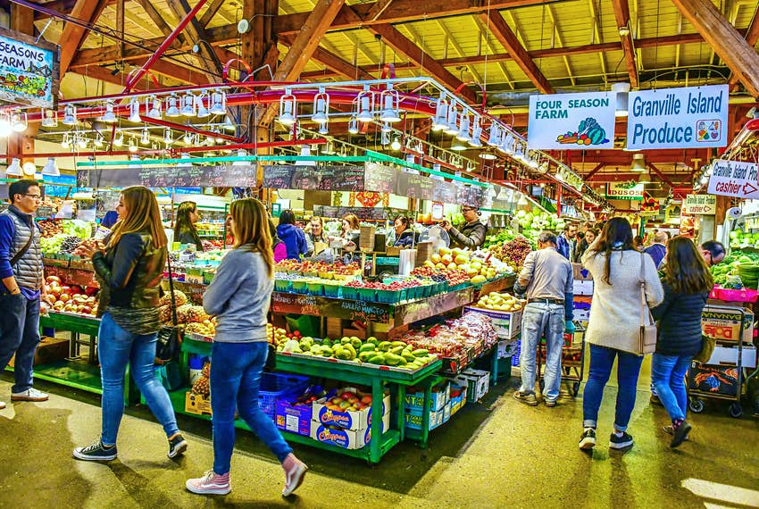 People walk through a fruit and vegetable market.