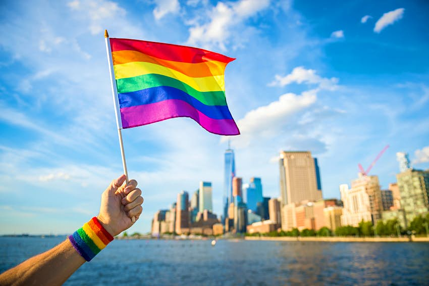 Hand holding up a colourful rainbow gay pride flag waving in the breeze with the New York City skyline in the background.