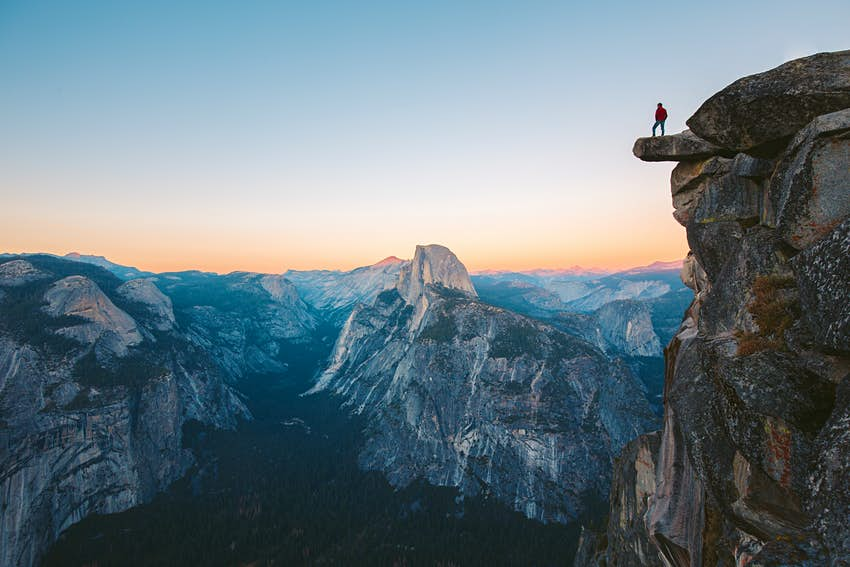 Hiker standing on an overhanging rock in Yosemite National Park