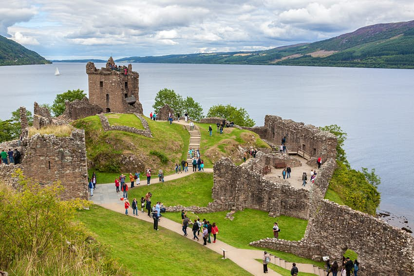 An aerial shot of a ruined castle with many visitors on the edge of a loch